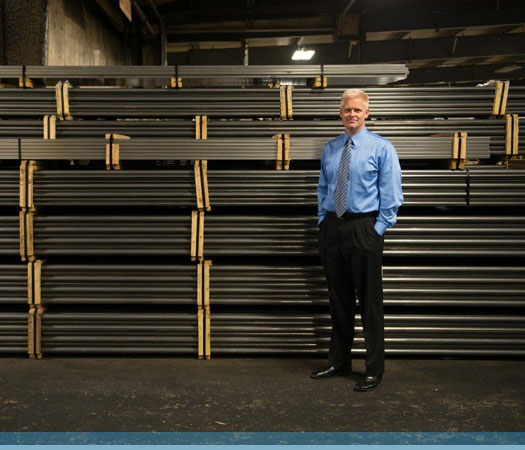 T&B Tube president, Jack Jones, standing in front of a display steel tubes.